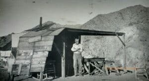 A man stands with his arms crossed outside of a shack with a mountain in the background.
