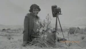 A woman sits near a desert lily and old camera in the desert.