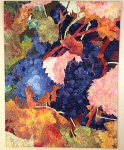 A colorful quilt with green, orange, and pink leaves and purple grapes.
