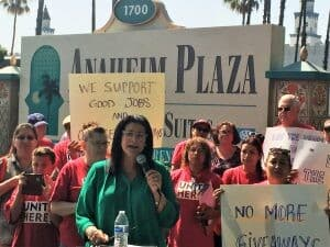 "A woman holds a microphone at a rally in a plaza. A sign behind her says ""We support good jobs."""