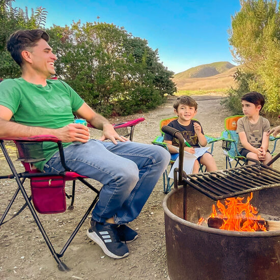 Man and two boys sitting by campfire