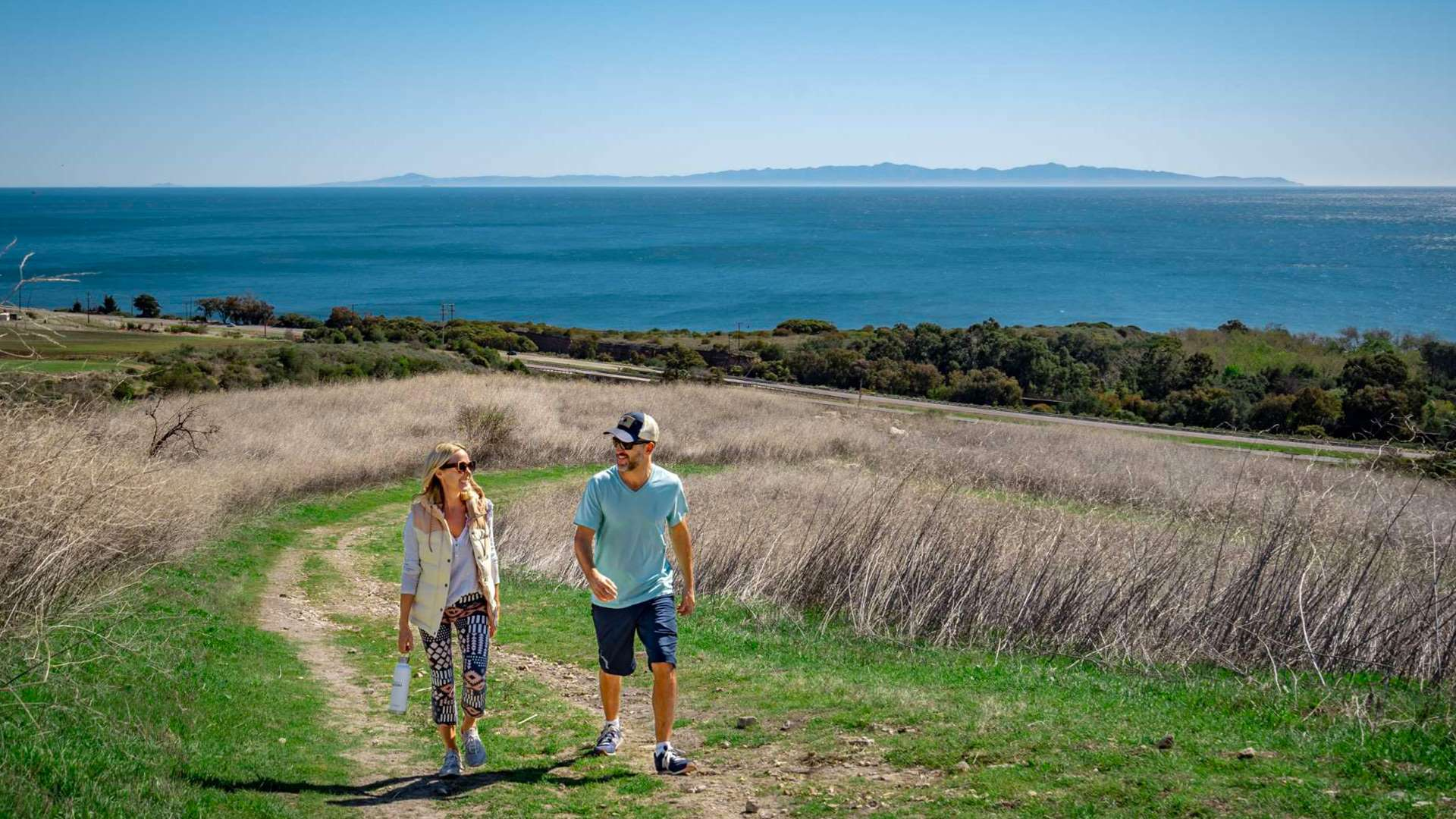 woman and man walking on trail