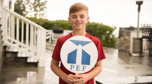 boy holding PEF sign