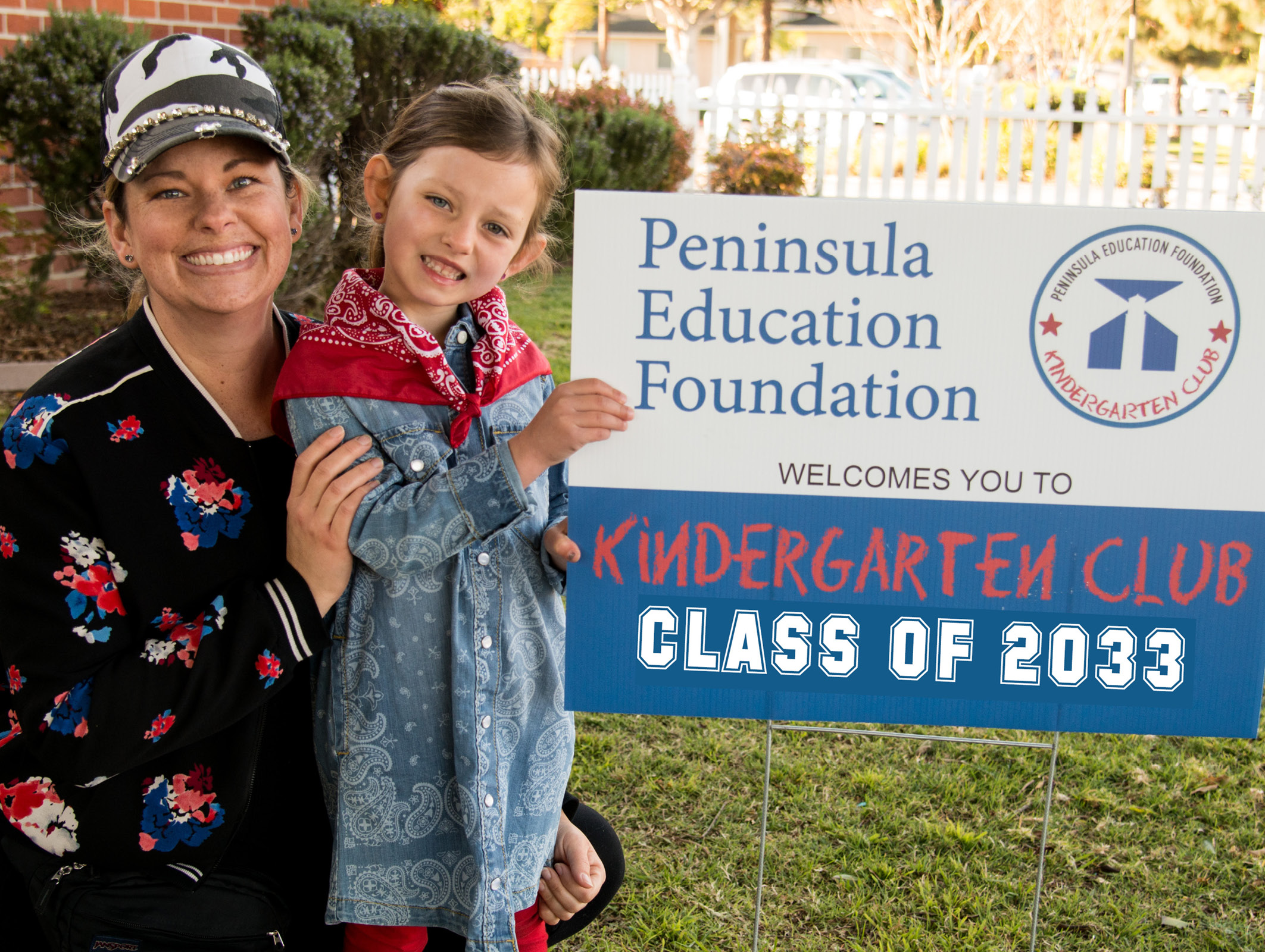 Mother and little girl holding PEF Kindergarten Club sign