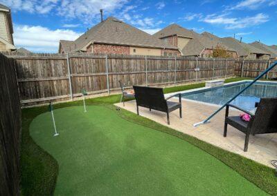 Backyard putting green next to a pool