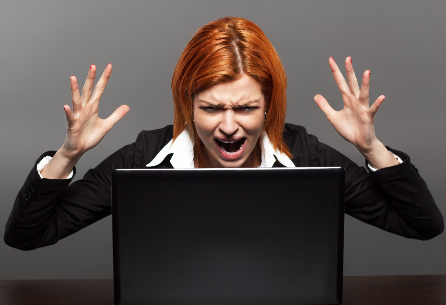 Angry woman screams at her laptop