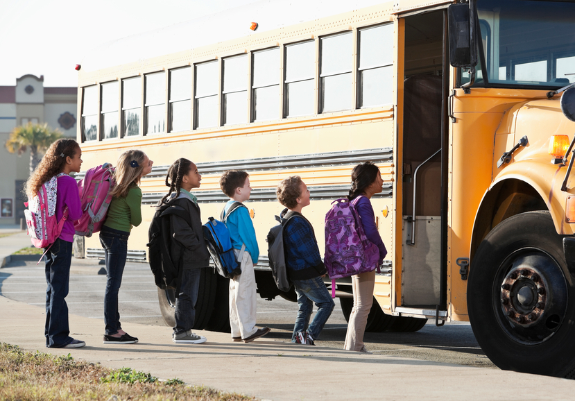 Line of children boarding school bus
