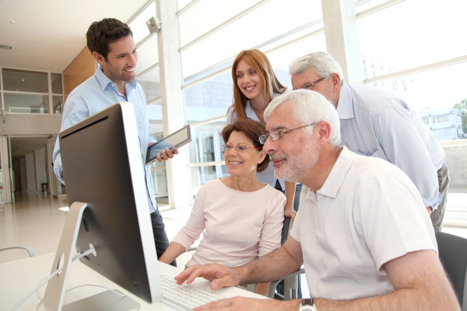 Group of senior people in front of desktop computer