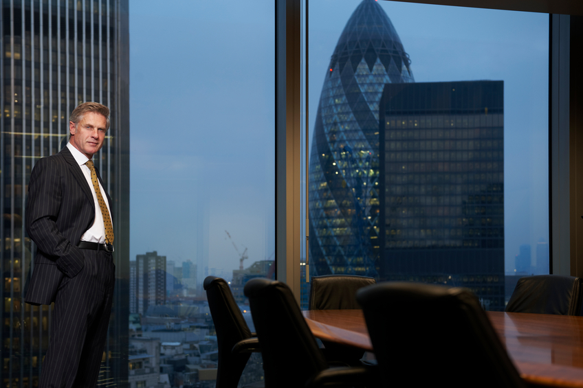 CEO standing office window with view of skyline