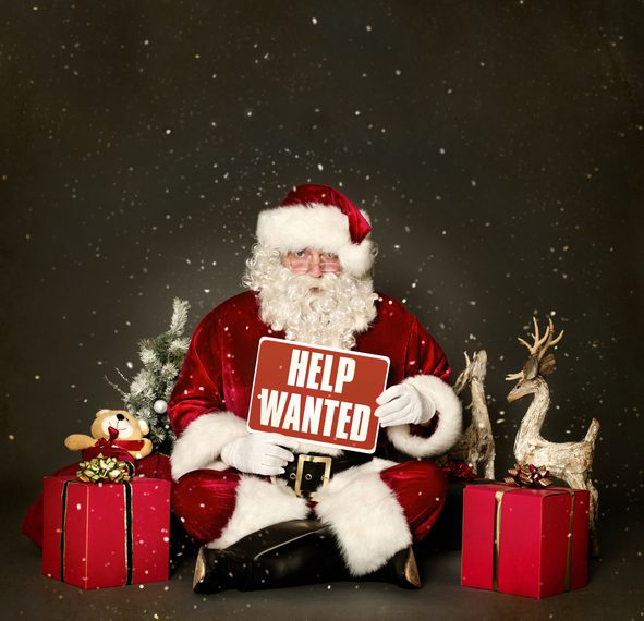 Santa Claus holding Help Wanted sign