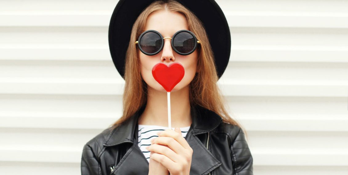 Woman holding heart shaped lollipop
