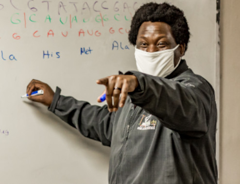 african american man masked pointing at students and white board
