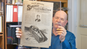 Steve Mayfield is a crime lab photographer and Mormon documentation collector. Here he is holding a newspaper from 1877 on John D. Lee execution.