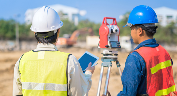 two men with land surveying equipment