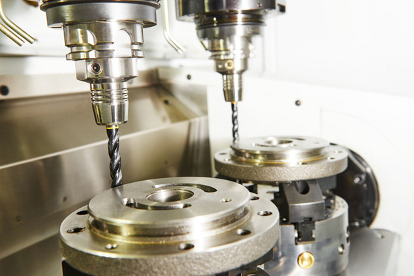Milling machine tool with two mills in chuck preparing to process metal detail at industrial manufacture factory