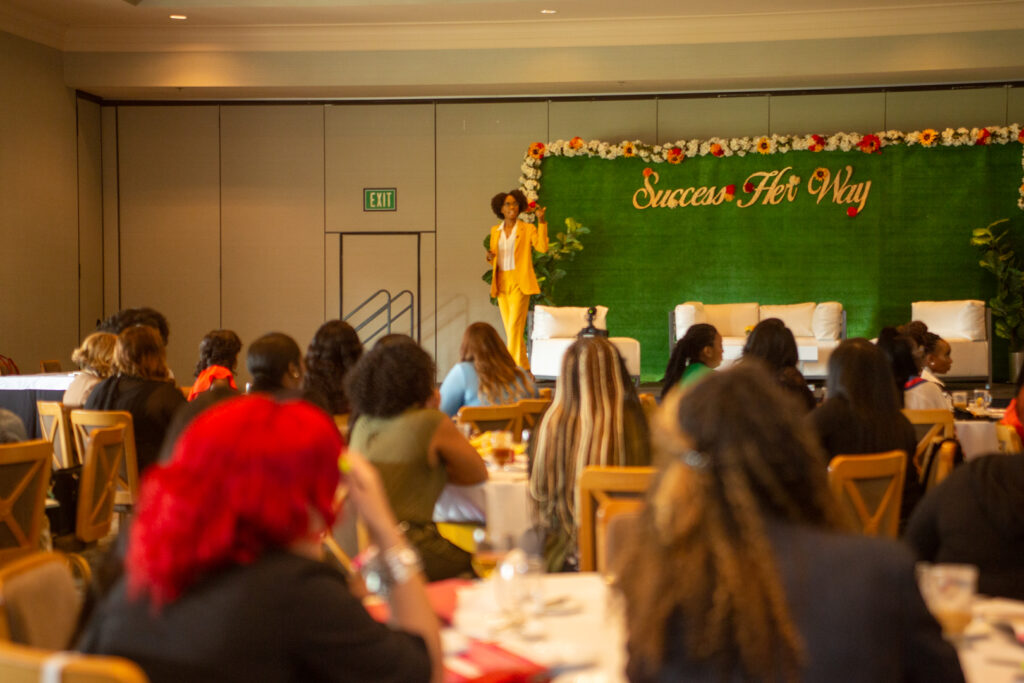 Emerald Sparks speaking onstage in yellow pants suit to women in audience