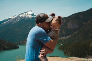 Father hugging daughter in his arms at a lake with mountains behind them