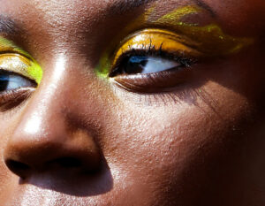 Close up on woman's eyes with fluorescent yellow graphic eyeliner