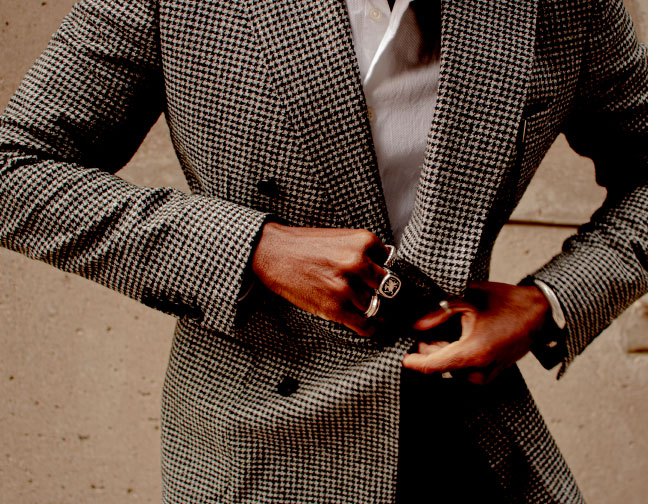 Portrait of Denzel Coke, who wears a houndstooth jacket and several bold rings.