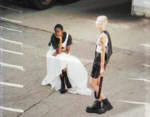 A photograph of two models in a parking lot wearing garments from pilotszn's debut collection.