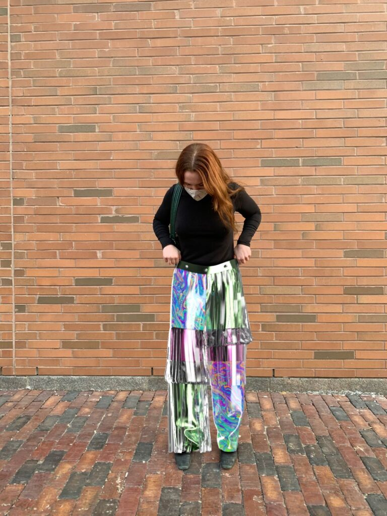 Jessi standing outside wearing digital holographic pants.