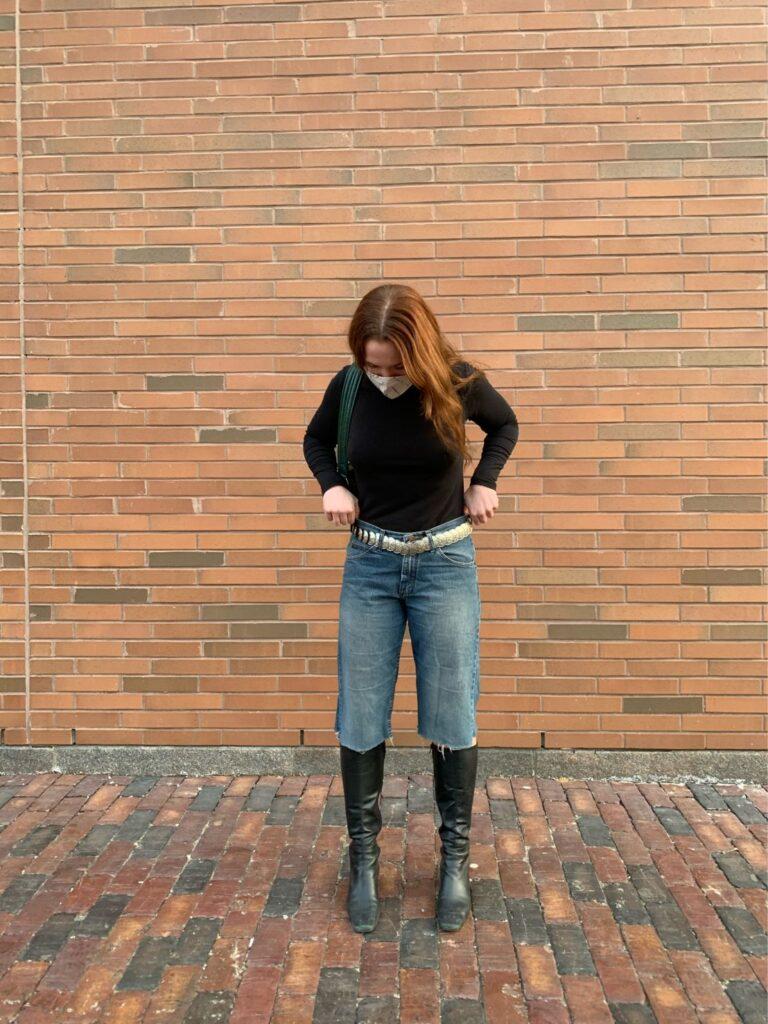 Jessi standing outside wearing denim cut-off shorts.