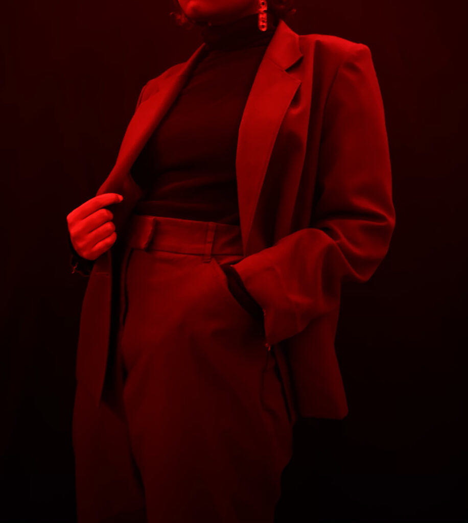 Tamia is wearing a turtleneck from Urban Planet and a thrifted red suit.