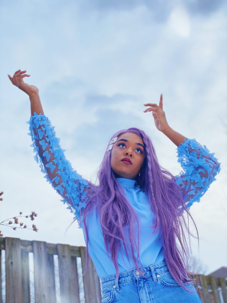 Maya is wearing a blue blouse from SHEIN, hair clips from wowyesh, mom jeans from H&M and purple wig from FOXWIGS.