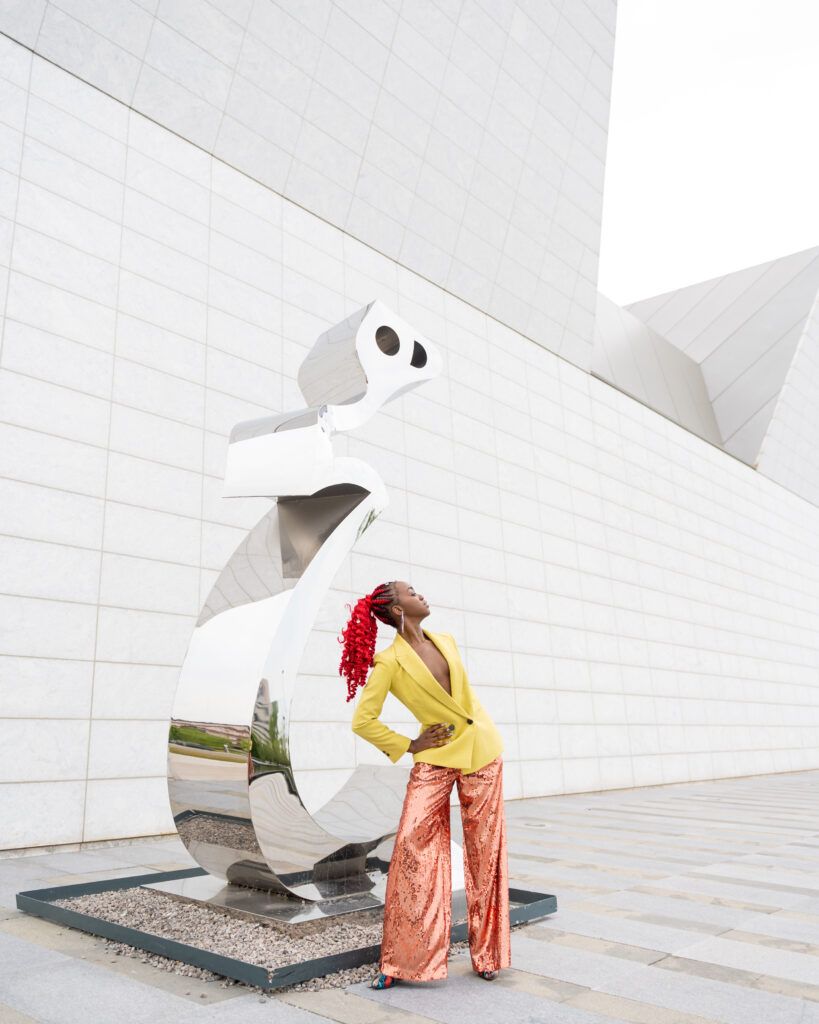 A black woman with curly red hair in a ponytail, posing with an abstract sculpture