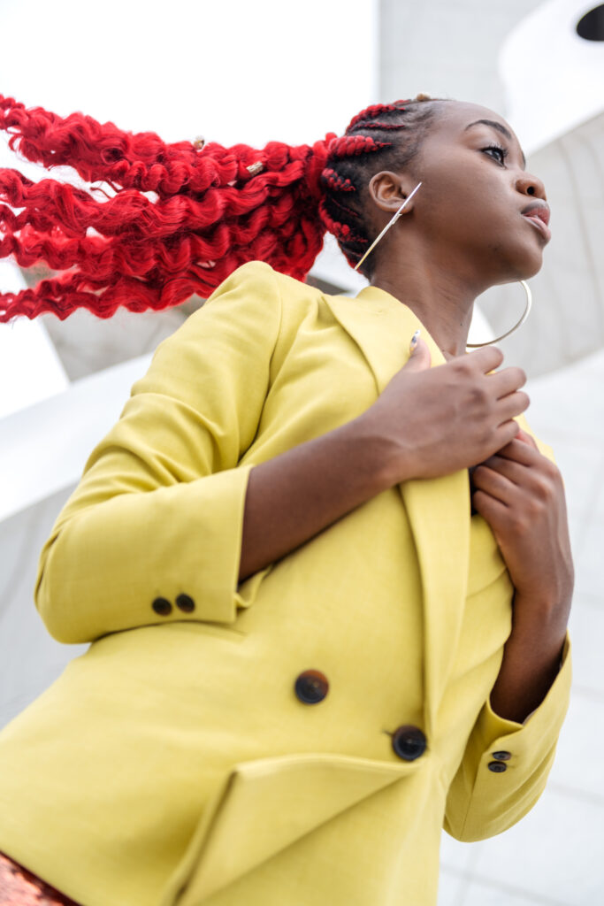 Close-up of a black woman flipping her curly red ponytail, wearing a lime blazer