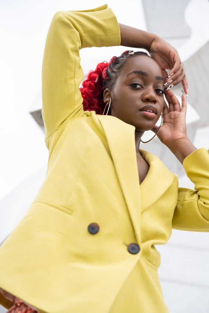 Close-up of a black woman wearing a lime blazer, framing her face with her hands