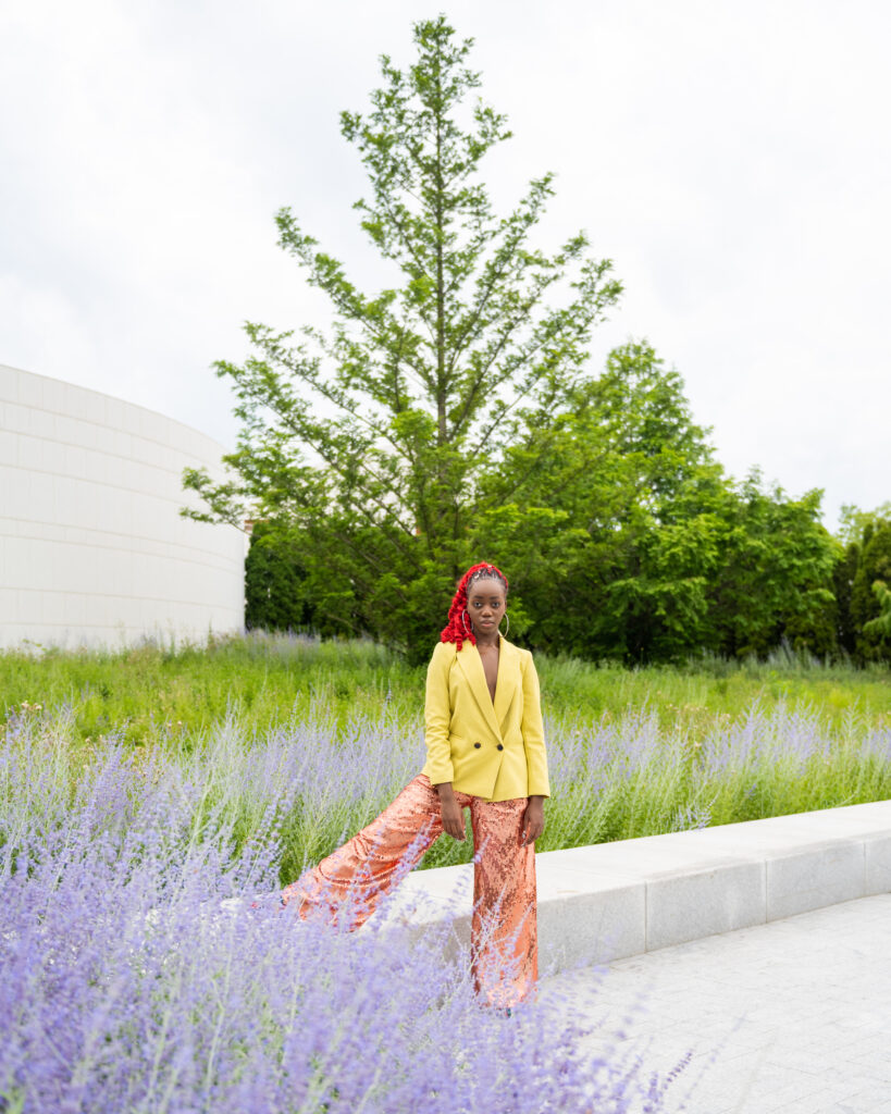 A black woman wearing a red ponytail, posing among lavender plants and greenery