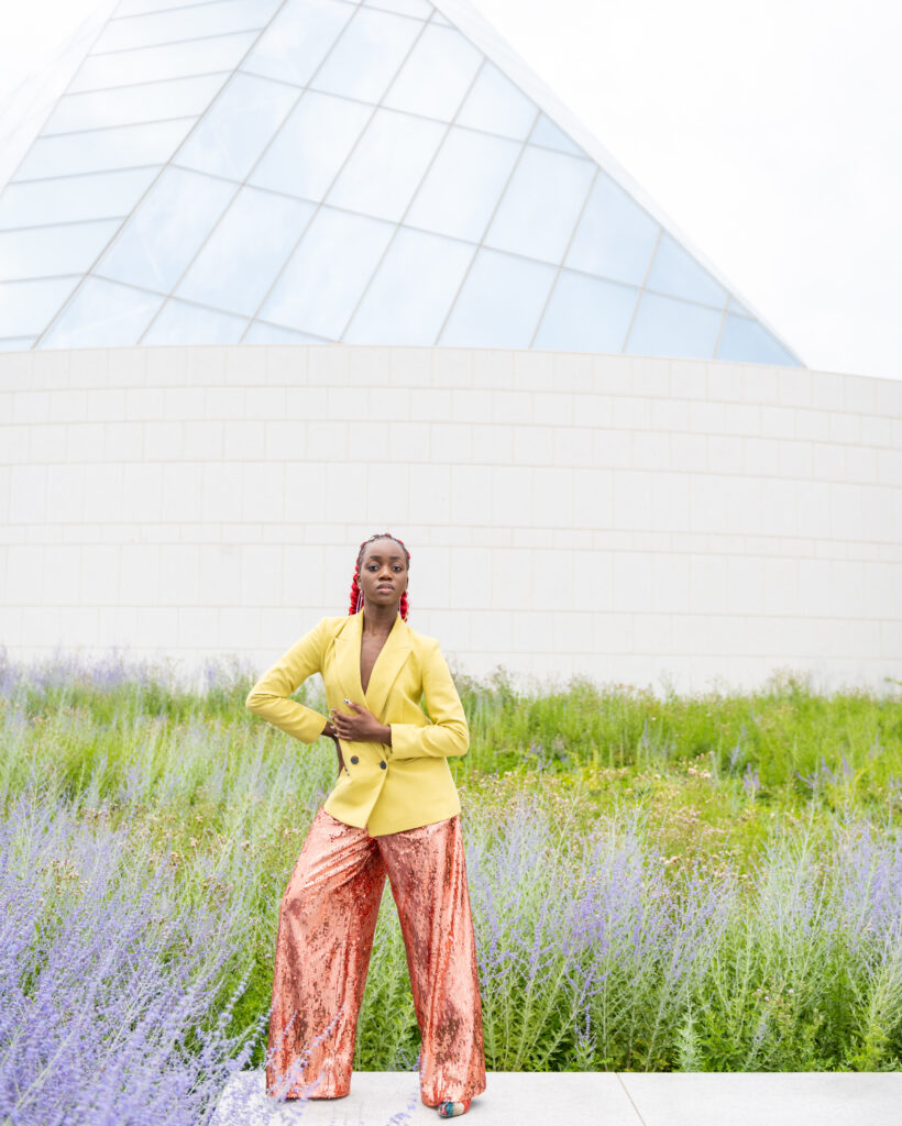 A black woman wearing a ponytail, posing among lavender plants and greenery
