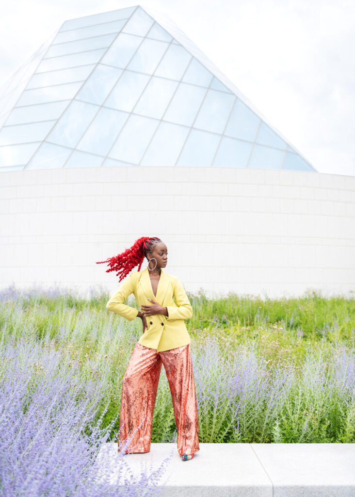 A black woman flipping her red ponytail, posing among lavender plants and greenery