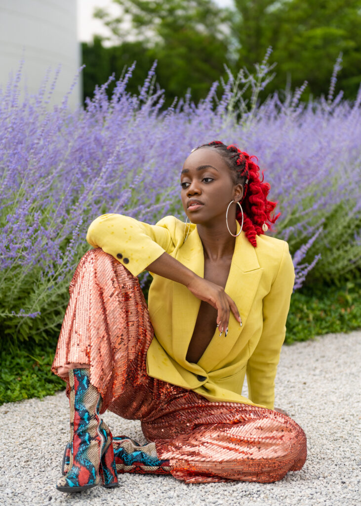 A black woman in a red ponytail, sitting on pebbled ground in front of lavender plants