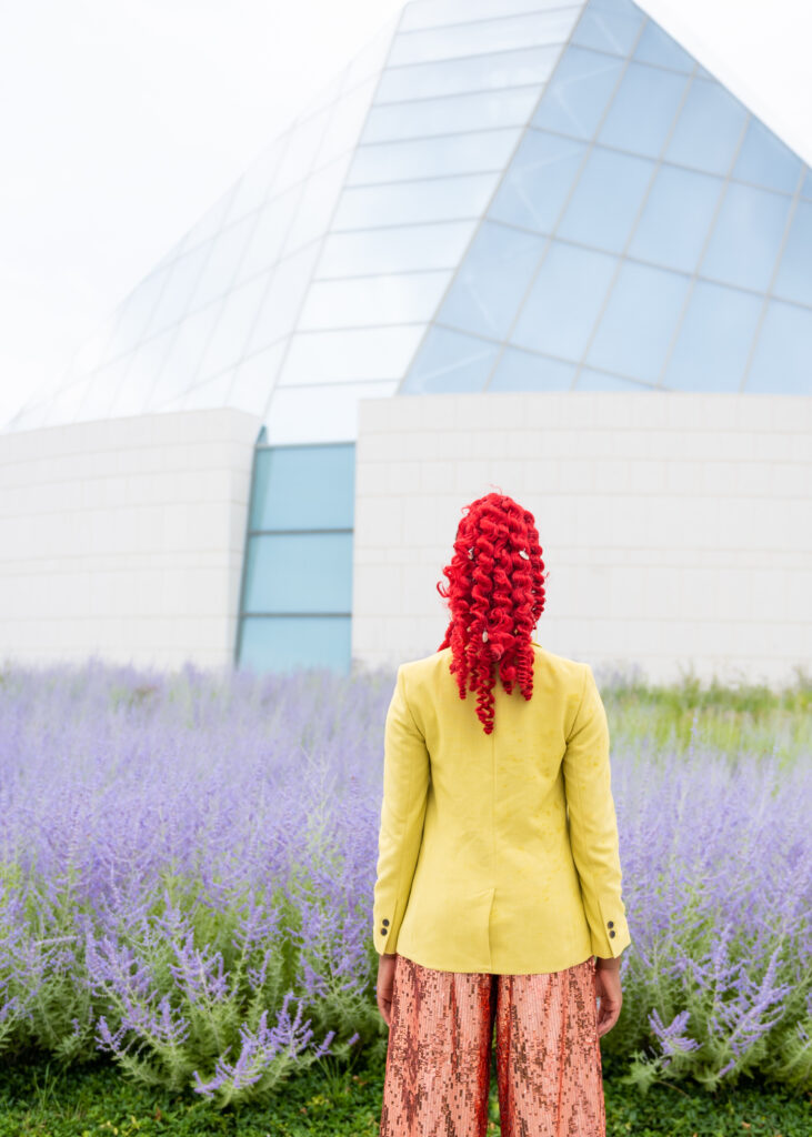 Close-up of a black woman in a red ponytail with her back to the camera, wearing a blazer