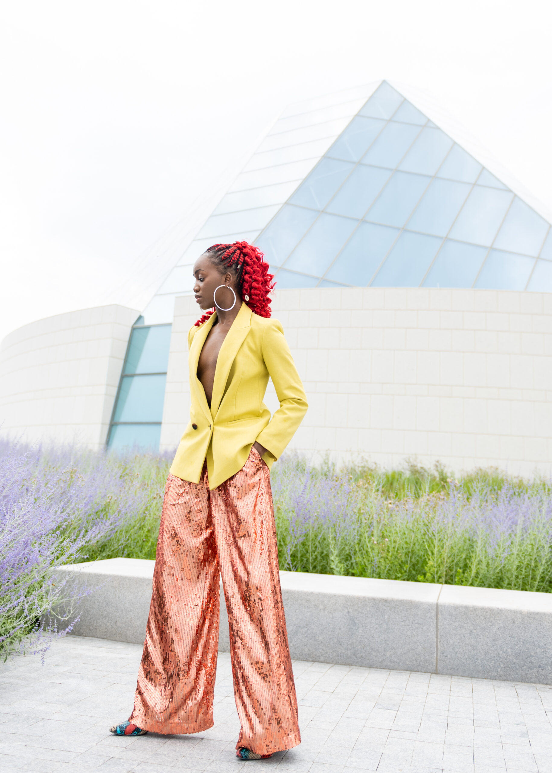A black woman in a red ponytail leaning away from the camera, her hands in pant pockets