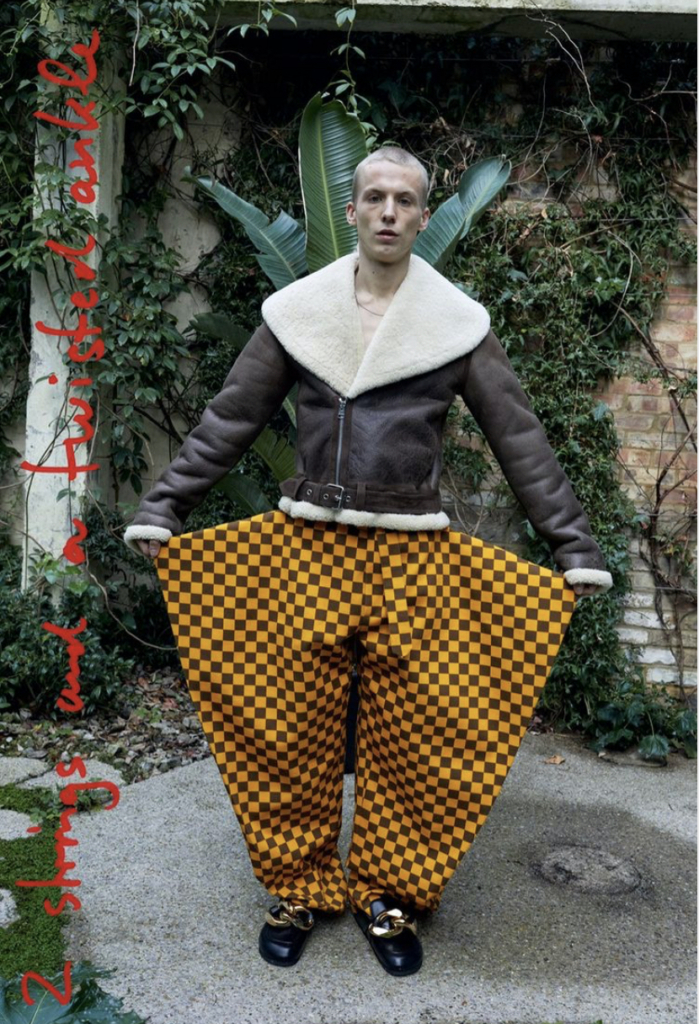 JW Anderson F/W 2021 collection, man in yellow and brown checked pants and sherpa fleece jacket.