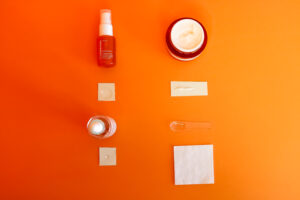 Tonal flat lay photograph of 3 skincare products and an orange against a solid orange coloured background.