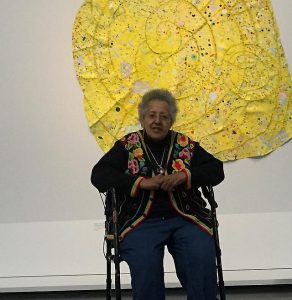 Howardene Pindell sits in front of Nautilus, (2014-15, mixed media on canvas from the Jacqueline Bradley and Clarence Otis Collection. Photos by Jodie Jacobs