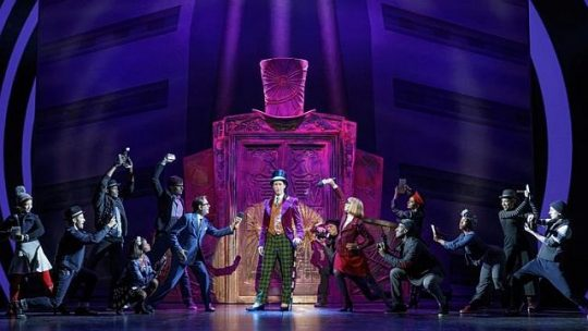 Noah Weisberg as Willy Wonka and company in Charlie and the Chocolate Factory. (Photo by Joan Marcus)