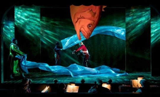 Among the tin soldier's travails is to be eaten by a fish but the fish brings him home in The Steadfast Tin Soldier at Lookingglass Theatre.