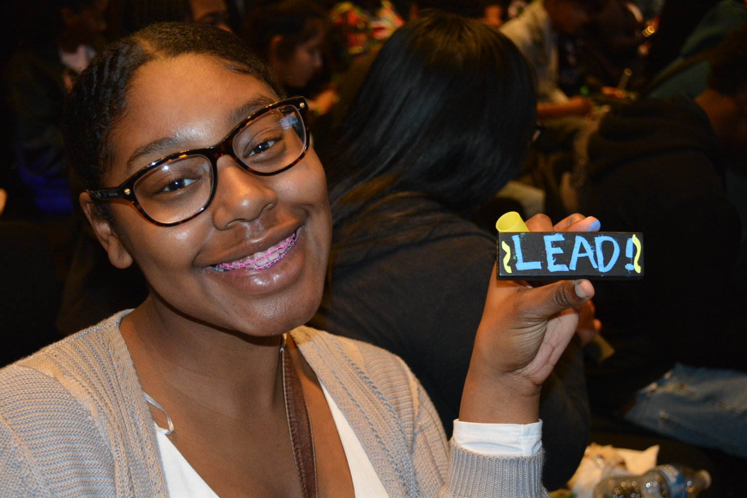 """A young student holds up a """"LEAD"""" brick during a SPEAK assembly"""