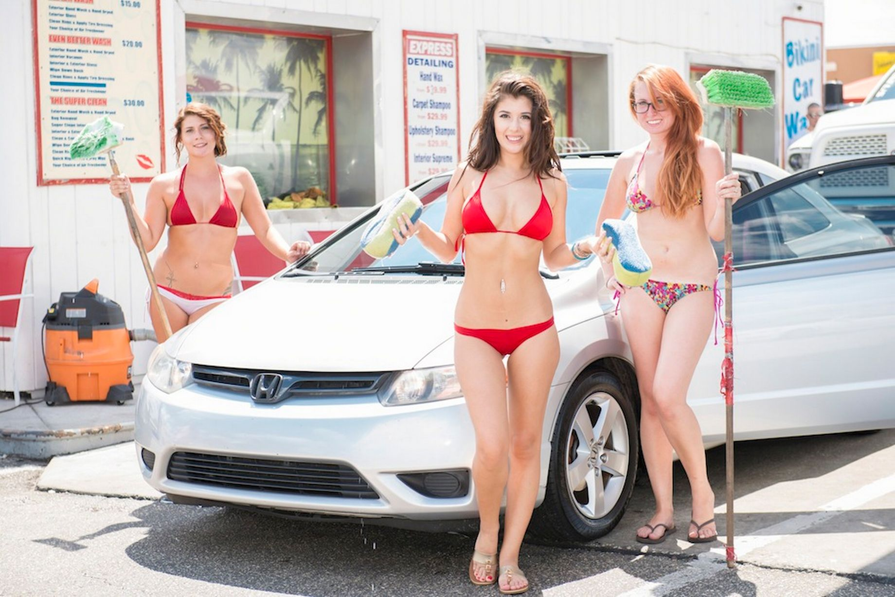 three girls washing a car red bikini redhead glasses