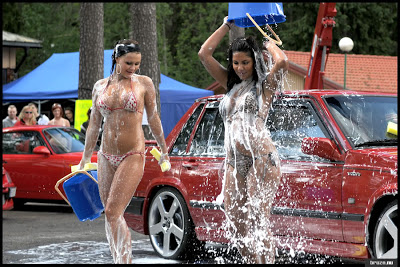 girl dousing herself with bucket of water car wash