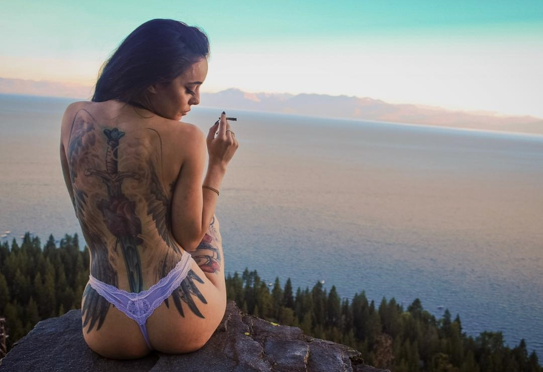 near naked girl on peak with joint