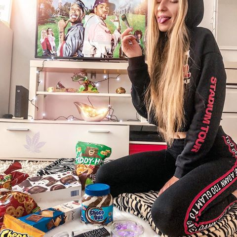 goofy party stoner girl in her room with goodies