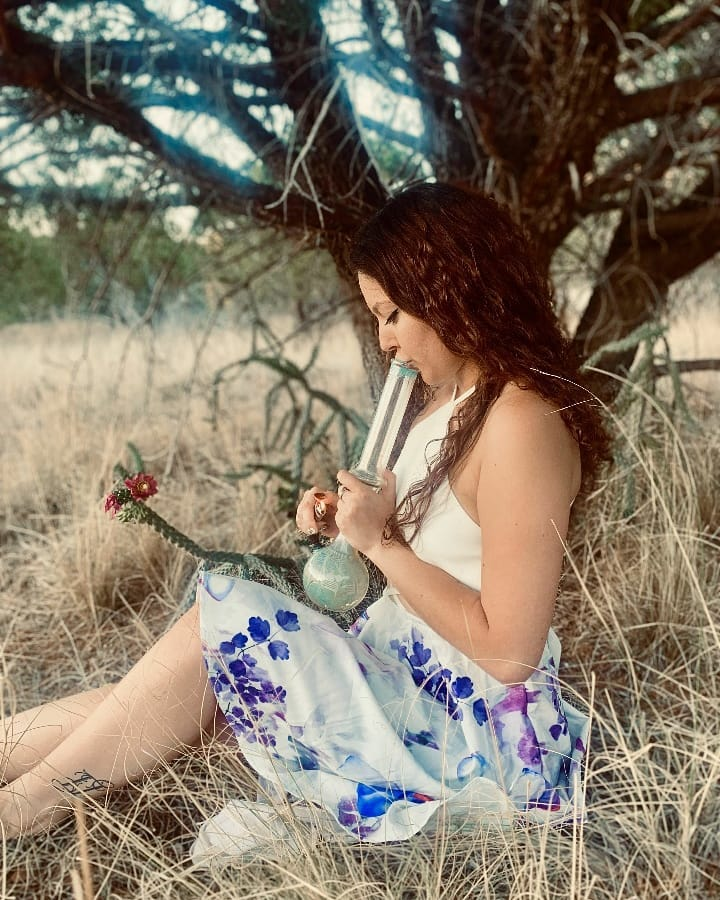 brunette girl under tree with a bong