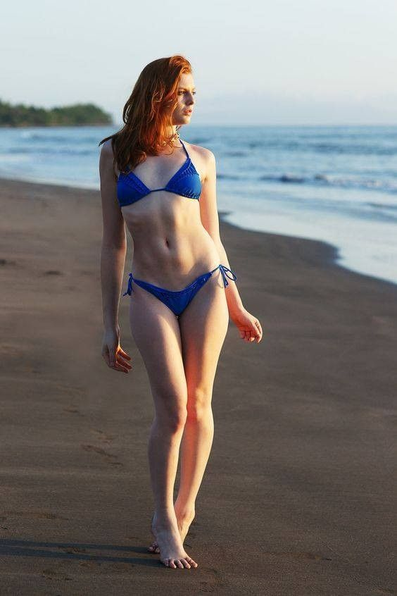 tall thin redhead on the beach walking