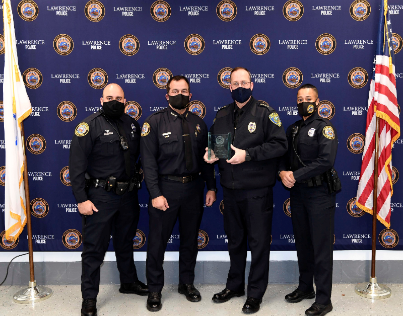 Four uniformed police officers accepting award